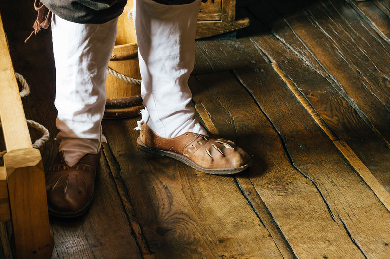 Man wearing old style shoes on a wooden floor Casual Clothing Clothes Costume Day Footwear Historic Indoors  Leggings Leisure Activity Lifestyles Low Section Man Person Shoes Standing Warm Wooden Wooden Floor