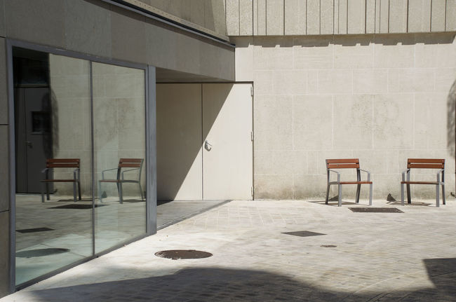 Two empty chairs in a courtyard reflected in patio doors Architecture Built Structure Chair Day Empty Empty Chairs Indoors  No People Reflection Sliding Door Space Sunlight Window
