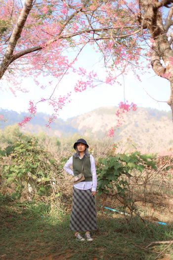 Full length of woman standing against cherry tree