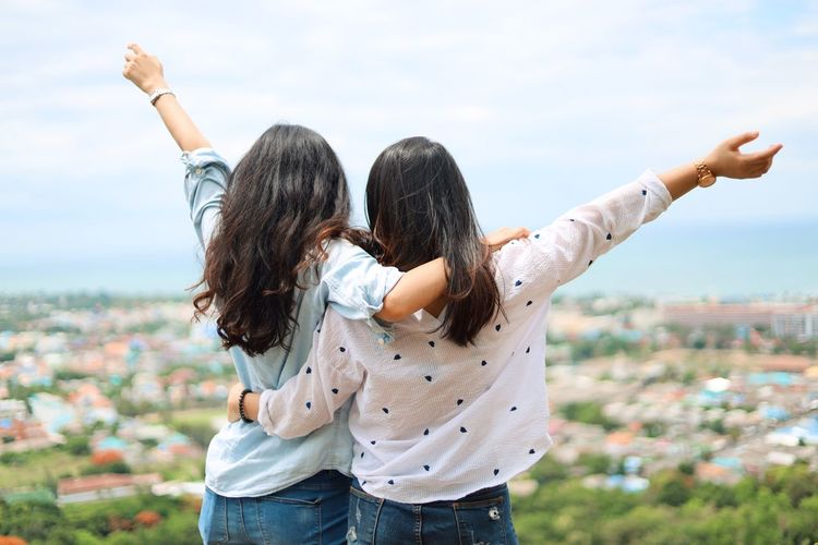 Two People Togetherness Bonding Positive Emotion Emotion Women Casual Clothing Real People Lifestyles Leisure Activity Rear View Human Arm Love Adult Focus On Foreground Three Quarter Length Sky Friendship Young Women Family Hair Arms Raised Outdoors Hairstyle