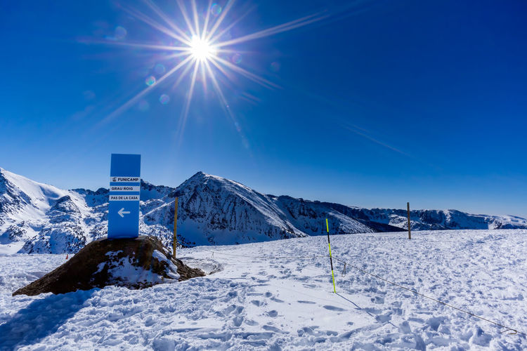 Scenic view of snow covered mountains against blue sky on sunny day
