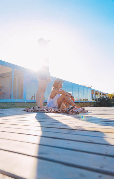 Architecture Building Exterior Built Structure Clear Sky Day Friendship Full Length Leisure Activity Lens Flare Lifestyles Outdoors People Real People Shadow Skateboard Park Sky Summer Sunlight Swimming Pool Togetherness Two People Vacations Water Young Adult Young Women