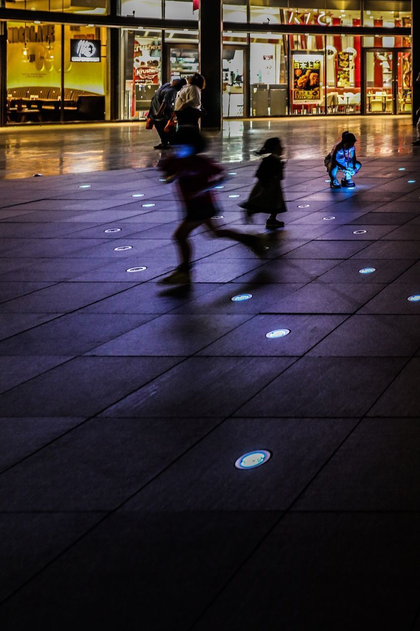 real people, group of people, lifestyles, men, motion, walking, architecture, people, built structure, blurred motion, night, women, city, transportation, street, adult, illuminated, full length, building exterior, flooring, outdoors, tiled floor, paving stone