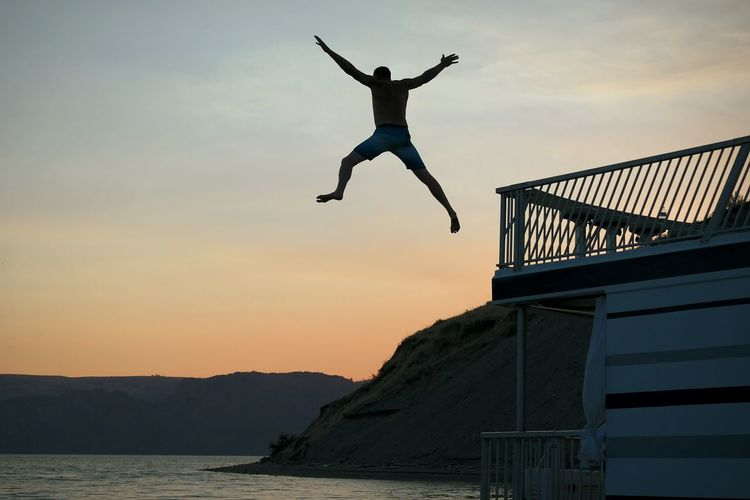 Man jumping in sea against sky during sunset