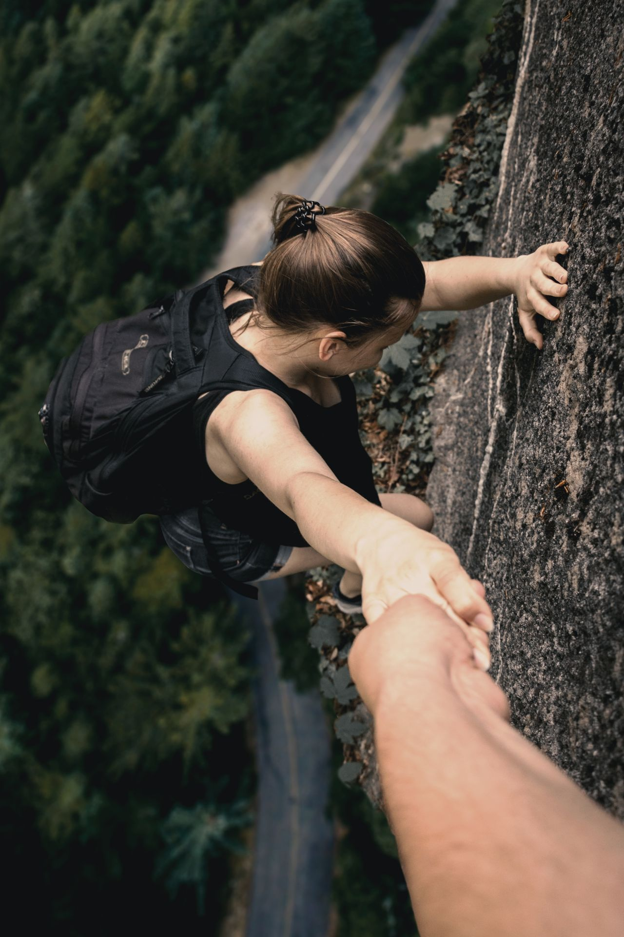 Cropped hand holding young backpack woman climbing on cliff