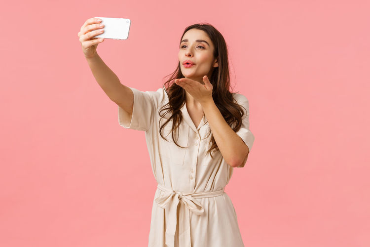 Full length of young woman photographing against pink background