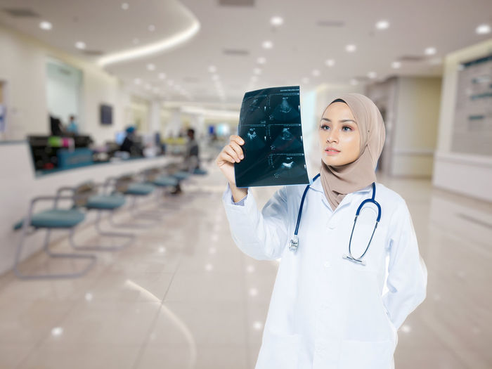 Adult Clothing Communication Doctor  Focus On Foreground Front View Healthcare And Medicine Holding Indoors  Lab Coat Medical Instrument Medical Supplies One Person Portable Information Device Responsibility Standing Stethoscope  Technology Waist Up Wireless Technology Women