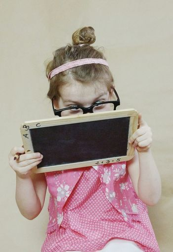Girl looking at blackboard while sitting against wall