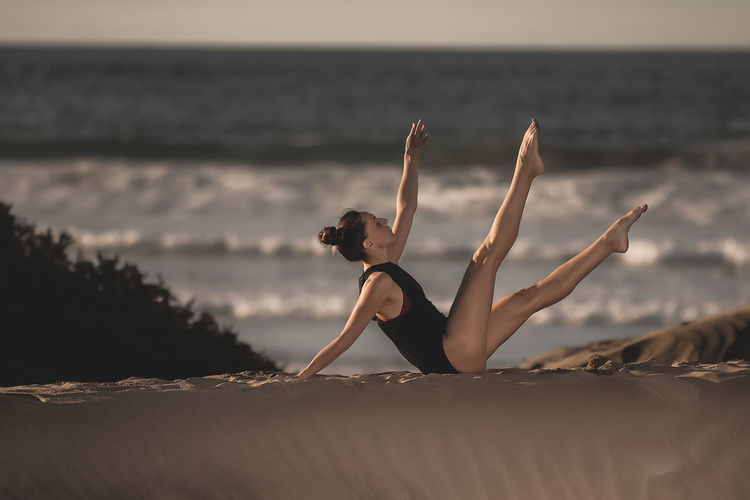 Fit woman practicing yoga on seashore Woman Yoga Beach Practice Asana Pose Sky Young Adult Lifestyles Sea Land Young Women Real People Leisure Activity One Person Clothing Full Length Bikini Beauty Horizon Over Water Nature Water Side View Adult Beautiful Woman