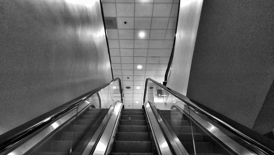 Low angle view of escalator against tiled ceiling