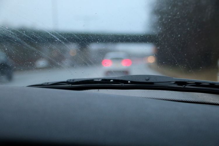Car on road seen through wet window