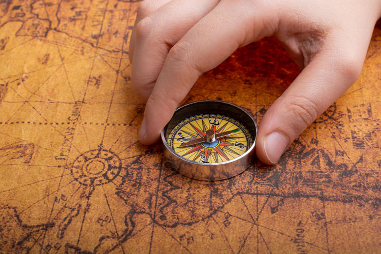 Adventure Antique Arrow Background Circle Compass Direction Discovery East Equipment Exploration Geography Guide Hand Holding Isolated Journey Latitude Longitude Magnet Magnetic Map Metal Nautical Navigation North Object Old Orientation Retro South Studio Shot Tool Topography Tourism Travel Trip Vintage West White World