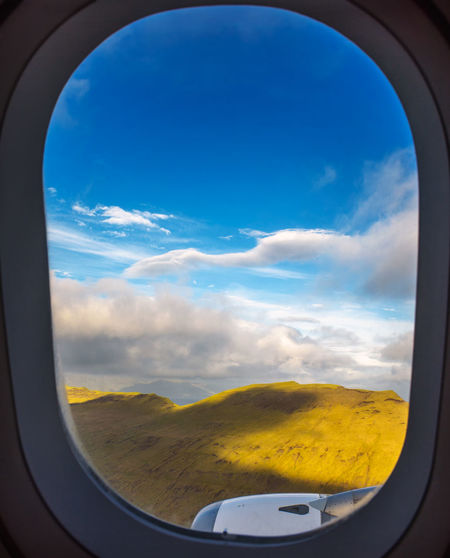 Scenic view of landscape against sky seen through airplane window
