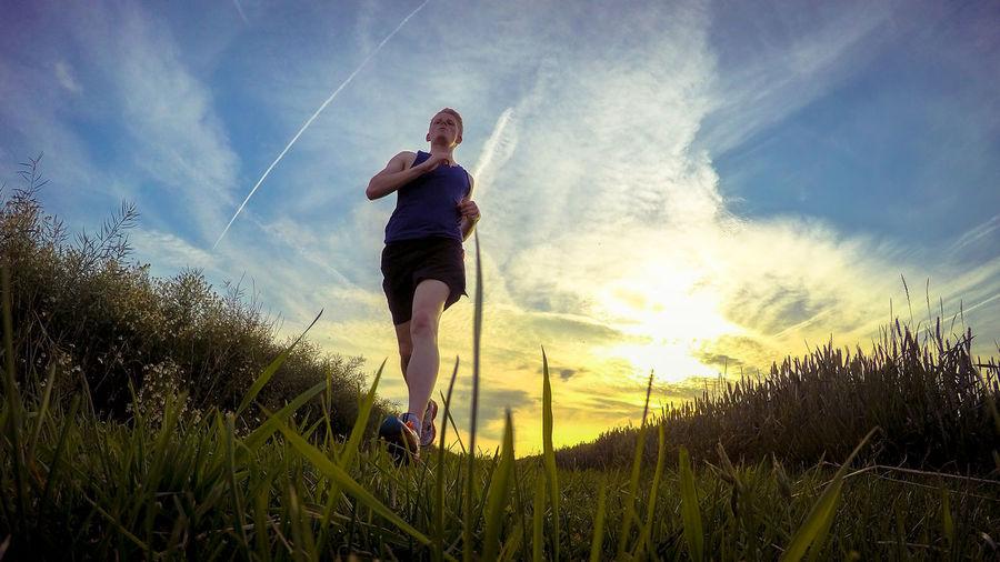Full Length Of Man Exercising On Field During Sunset
