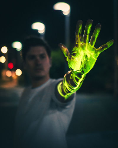 Young Man Showing Green Glowing Hand At Night
