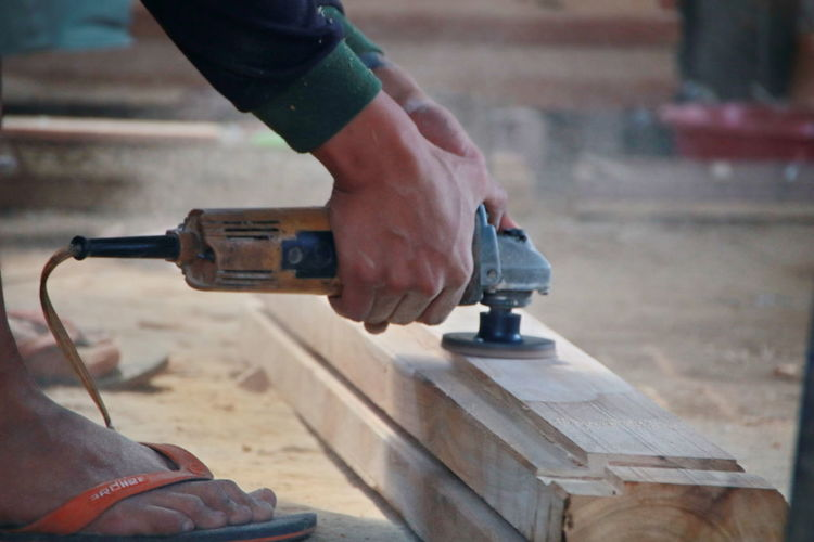 Low section of man working on wood in workshop