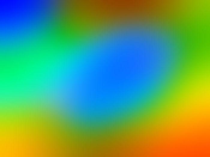 Defocused image of rainbow against yellow blue sky