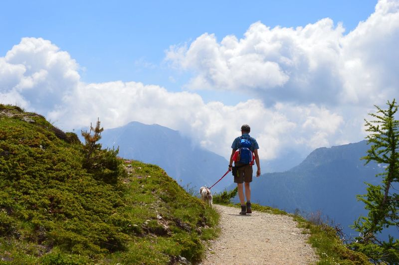 Rear view of man with dog walking on mountain against sky