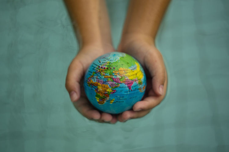 Above close up looking down on hands holding the world over water Hand Holding Hands India Map Middle East NGO Plant Power Africa Cat Continent Ecology Energy Ethnic Europe Ocean Planet Protection Refugees Sustainability Sustainable Sustainable Resources Unicef Water World