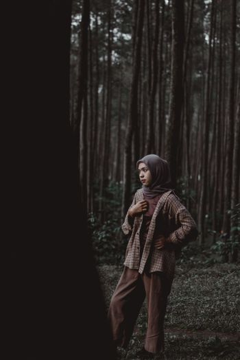 Young woman wearing hijab while standing in forest