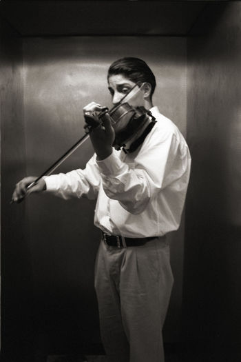 Man playing violin while standing in elevator