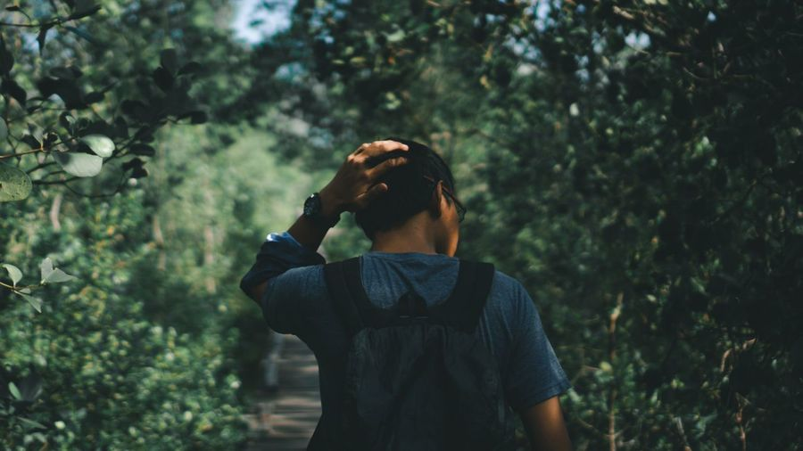 Full length of teenage man standing by tree in forest alone and stressed