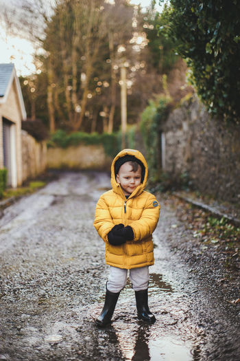 Portrait of boy standing on footpath during winter