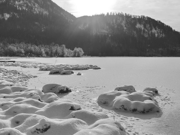 Scenic view on a frozen lake against the sun in the bavarian alps