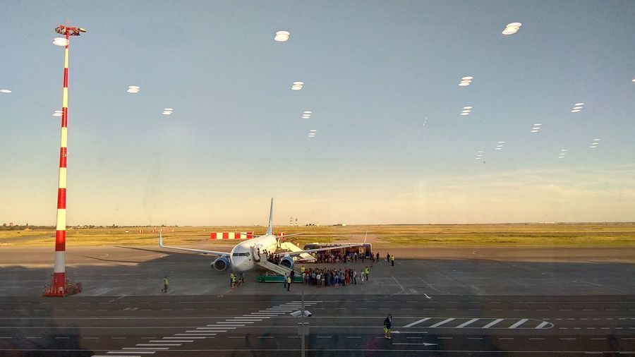 People by airplane on airport runway against sky seen through glass window with reflection