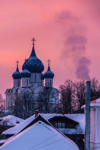 Pink sunset in Suzdal, a small town near the Russian city of Vladimir, an open air museum part of the Golden Ring of Historical Russian cities with the traditional onion shape dome orthodox churches Architecture Winter Building Exterior Cold Temperature Snow Sky Sunset Place Of Worship Spirituality Belief Religion No People Cloud - Sky Purple Pink Sunset Suzdal Vladimir Golden Ring Tourist Destination Tradition Culture Open Air Museum