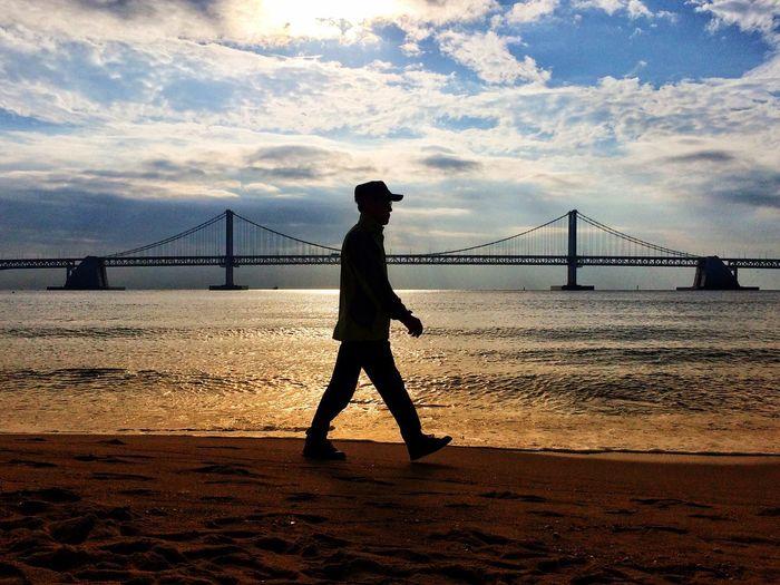 Full length of man standing on suspension bridge over river