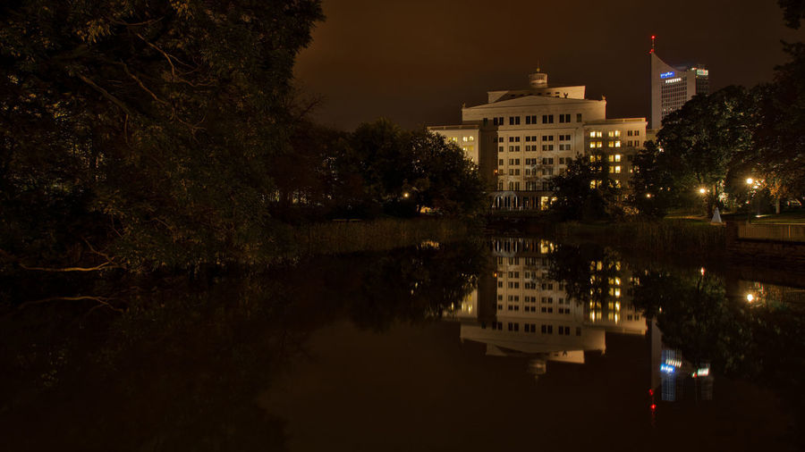 Reflection of buildings in lake at night