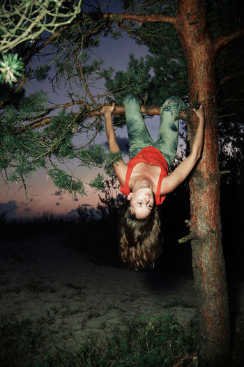 Young woman hanging on branch