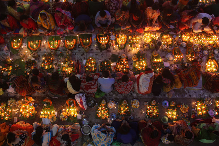 Directly above shot of people with illuminated diyas during religious fasting at night