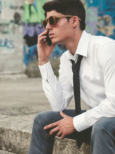 Young man using mobile phone while sitting on retaining wall