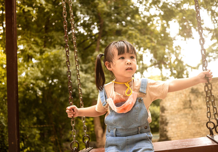 Portrait of girl on swing at playground