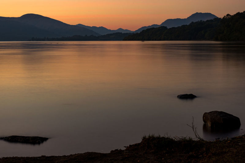 Late sunset overlooking Loch Lomond and Trossachs national park Scotland Landscape Mountain Sunset Lake Reflection Outdoors Mountain Range Silhouette Scenics No People Water Nature Beauty In Nature Sky Day Rocks Beach Loch Lomond Ben Lomond Hills Iconic Famous Place Freshwater Stunning Beautiful