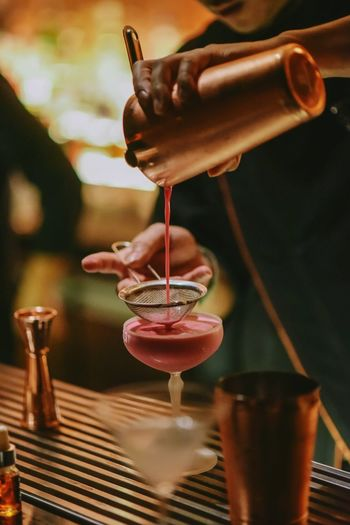 Midsection of bartender pouring cocktail in glass