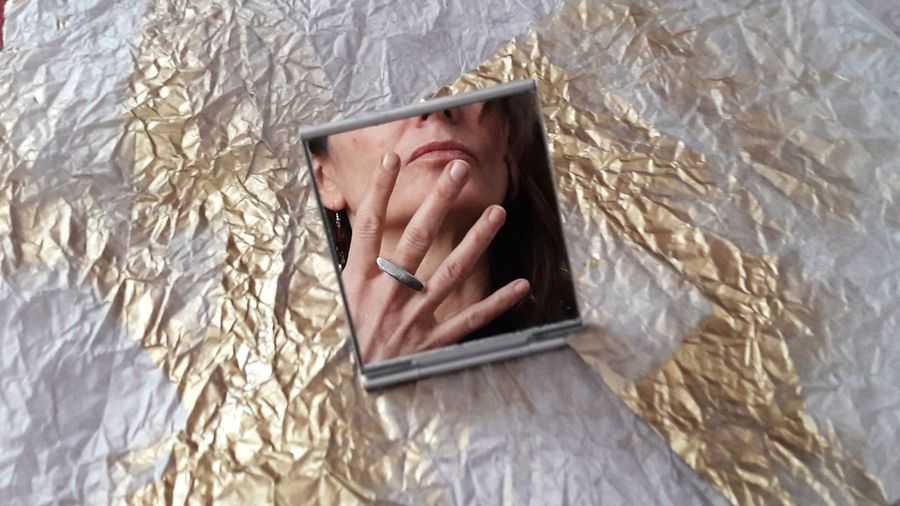 Reflection of woman showing ring in mirror over papers