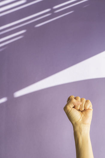 Cropped hand of woman against wall at home