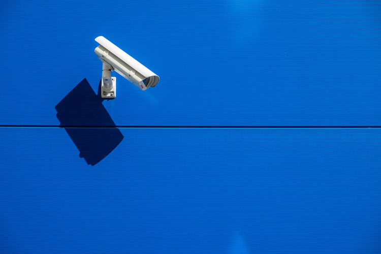 Close-Up Of Security Camera Mounted On Blue Wall