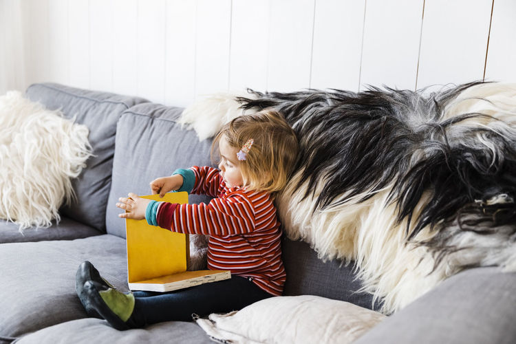 Girl sitting by fur on sofa at home