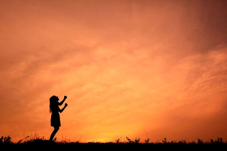 Silhouette of woman punching air at sunset