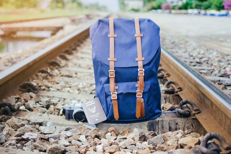Close-up of backpack and camera with passport on railroad track