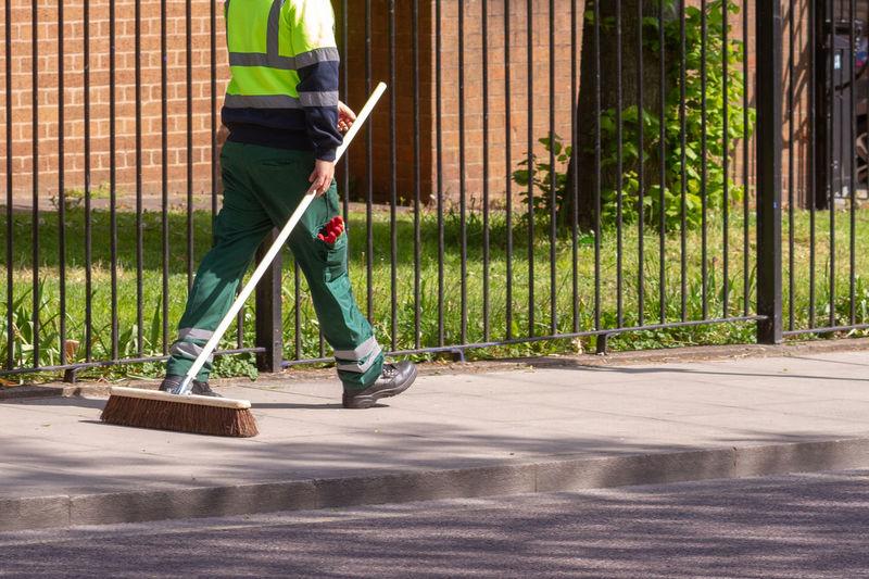 Street cleaner walking with his broom along clean streets in hackney, london