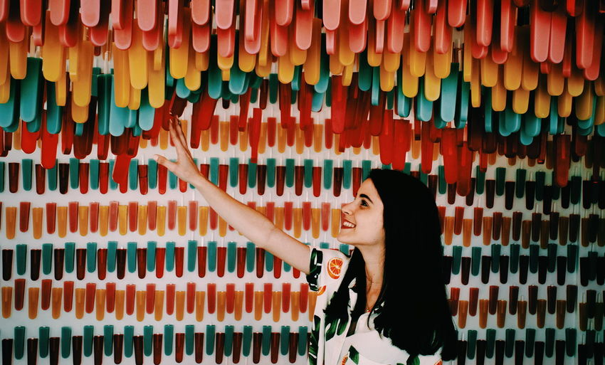 Full length portrait of woman standing against multi colored umbrellas