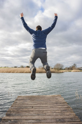 Young adult jumping on the edge of a dock Man Jumping Flying Jump Freedom Water Lake Action Dock Excitement Fly Happiness Happy Joy Landscape Lifestyles Males  Nature Outdoors People RISK River Sky Stress Success Feelings Winner Desperate