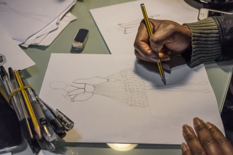 Cropped Hands Of Female Fashion Designer Drawing On Paper At Desk