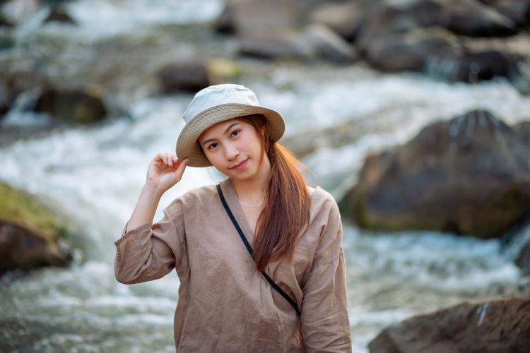 Portrait of beautiful young woman standing on rock