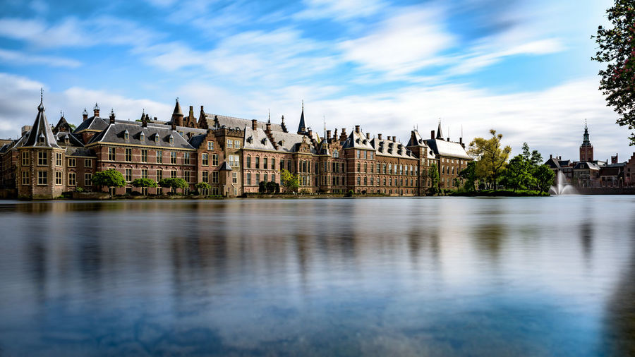 Binnenhof in front of river against cloudy blue sky
